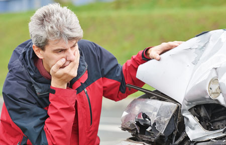 Man inspecting his car after an accident