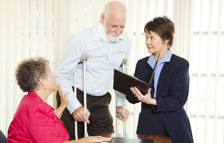 Man on crutches looks at paperwork with lawyer and woman present